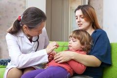 Pediatra que examina 2 años de bebé Imagenes de archivo