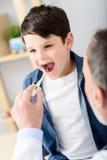 Pediatra que verifica a temperatura do paciente doente foto de stock