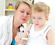 Pediatra que visita de la niña linda Imagen de archivo libre de regalías