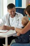 Pediatra sonriente durante trabajo Imagenes de archivo