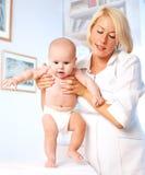 Pediatra y bebé de Doctror. Primeros pasos Imagenes de archivo