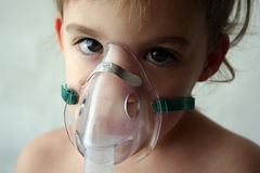 Pediatric Breathing Treatment. A little girl looks sad while taking her nebulizer breathing treatment Stock Photo