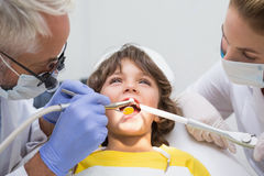 Pediatric dentist and assistant examining a little boys teeth Royalty Free Stock Image