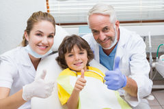 Pediatric dentist assistant and little boy all smiling at camera with thumbs up Royalty Free Stock Photography