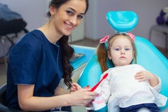 Pediatric dentist educating a smiling little girl about proper tooth-brushing, demonstrating on a model. Early Stock Image