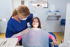 Pediatric dentist examining her smiling young patient Royalty Free Stock Photo