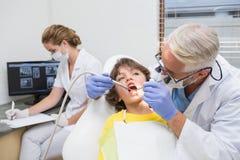 Pediatric dentist examining a little boys teeth with assistant behind Stock Photos