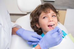 Pediatric dentist examining a little boys teeth in the dentists chair Stock Photos