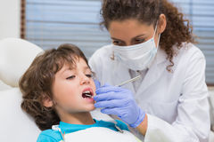 Pediatric dentist examining a little boys teeth in the dentists chair. At the dental clinic Royalty Free Stock Photography