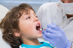 Pediatric dentist examining a little boys teeth in the dentists chair Stock Image