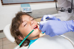 Pediatric dentist examining a little boys teeth in the dentists chair Royalty Free Stock Image