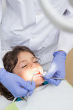 Pediatric dentist examining a little boys teeth in the dentists chair Stock Photos
