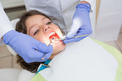 Pediatric dentist examining a little boys teeth in the dentists chair Royalty Free Stock Images