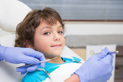 Pediatric dentist examining a little boys teeth in the dentists chair. At the dental clinic Stock Photography
