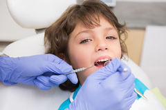 Pediatric dentist examining a little boys teeth in the dentists chair Stock Images