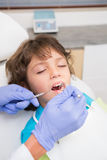 Pediatric dentist examining a little boys teeth in the dentists chair Stock Photography