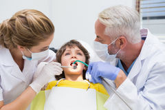 Pediatric dentist examining a little boys teeth with his assistant Royalty Free Stock Images