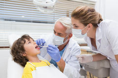 Pediatric dentist examining a little boys teeth with his assistant Royalty Free Stock Photography