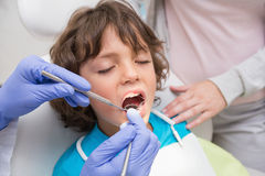 Pediatric dentist examining a little boys teeth with his mother Royalty Free Stock Photography