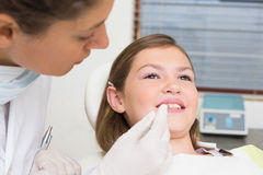 Pediatric dentist examining little girls teeth in the dentists chair Stock Image