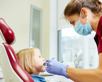 Pediatric dentist examining little girls teeth in Royalty Free Stock Image