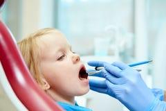 Pediatric dentist examining little girls teeth in Stock Images