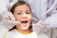 Pediatric dentist examining a patients teeth in the dentists chair Royalty Free Stock Image