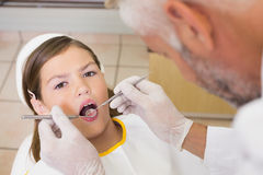 Pediatric dentist examining a patients teeth in the dentists chair Stock Photos