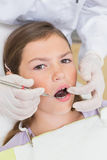 Pediatric dentist examining a patients teeth in the dentists chair Stock Photography