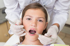 Pediatric dentist examining a patients teeth in the dentists chair Stock Image