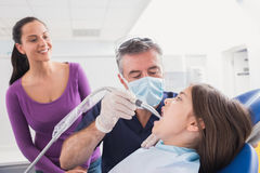 Pediatric dentist examining young patient with a suction tube Royalty Free Stock Photos