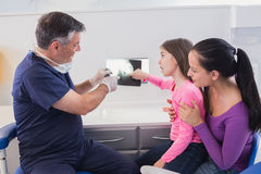 Pediatric dentist explaining to young patient and her mother the x-ray Royalty Free Stock Photos