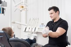 Pediatric dentist getting ready for treatment with young boy patient, wearing white gloves in dental office. Dentistry. Dental equipment Royalty Free Stock Photo