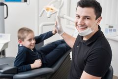 Pediatric dentist gives five young boy, congratulate patient for a successful treatment in dental office. Pediatric dentist shake hands with young boy Royalty Free Stock Photo