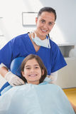 Pediatric dentist putting on her young patient the scrubs Stock Images