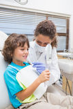 Pediatric dentist showing little boy his teeth in the mirror Royalty Free Stock Photo