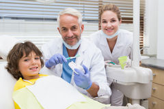 Pediatric dentist showing little boy how to brush his teeth Stock Image