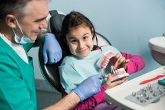 Pediatric dentist showing to girl in dentist chair dental jaw model at dental office. Dentistry, early prevention, oral hygiene concept royalty free stock photography