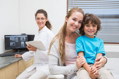 Pediatric dentist smiling at camera with little boy and his mother Stock Photography