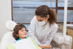 Pediatric dentist smiling down at little boy in chair Stock Images