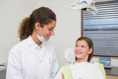 Pediatric dentist smiling with little girl in the chair Stock Photos
