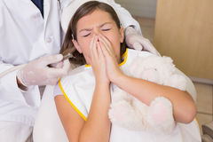 Pediatric dentist trying to see sneezing patients teeth Stock Image