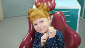 Pediatric dentistry concept. Charming little girl in dental chair. Lovely red-haired girl having fun at dental office