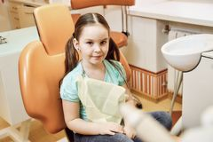 A little girl sitting on a chair in the dentist`s office stock photos