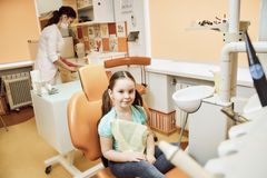 A little girl sitting on a chair in the dentist`s office stock images