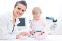 Pediatric doctor with baby on survey Royalty Free Stock Image