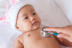 Pediatric doctor exams newborn baby girl with stethoscope in hos Stock Image