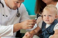 Pediatrician checking girl ears Royalty Free Stock Photo