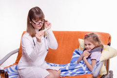 Pediatrician checks temperature on electronic thermometer sick child Stock Photography