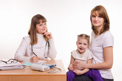Pediatrician, the child and his mother are sitting at the desk in the office Stock Photos